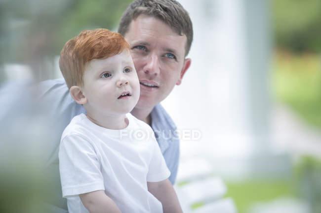Niño pelirrojo con padre afuera. - foto de stock