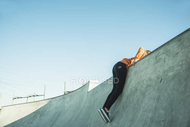 Girl in skatepark hanging on ramp — Stock Photo