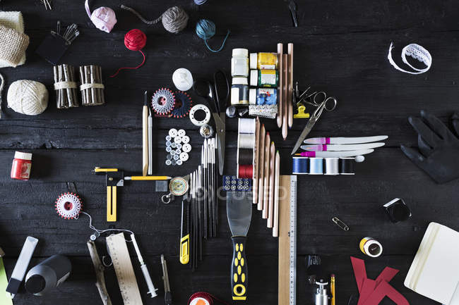 Arrangement of craft materials and tools on black wood — Stock Photo