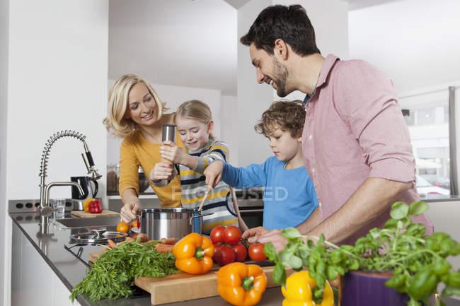 Feliz família caucasiana cozinhando na cozinha — Fotografia de Stock