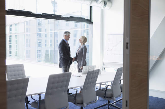 Businissman and businesswoman shaking hands in conference room — Stock Photo