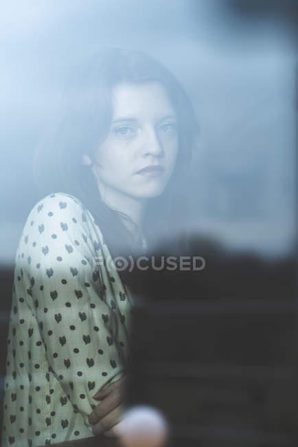 Серьезная молодая женщина за окном — стоковое фото
