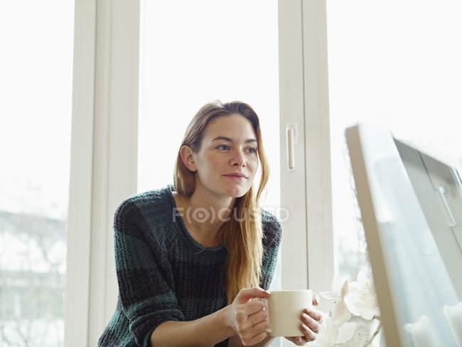 Jovem mulher sentada à janela, segurando xícara de café — Fotografia de Stock