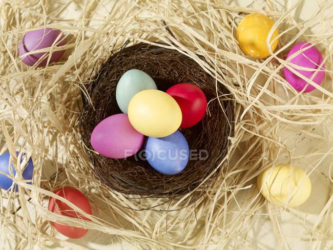 Ninho de Páscoa colorido com ovos coloridos e palha — Fotografia de Stock