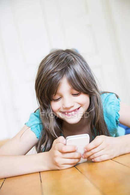 Lächelndes Mädchen liegt mit Smartphone auf Holzboden — Stockfoto