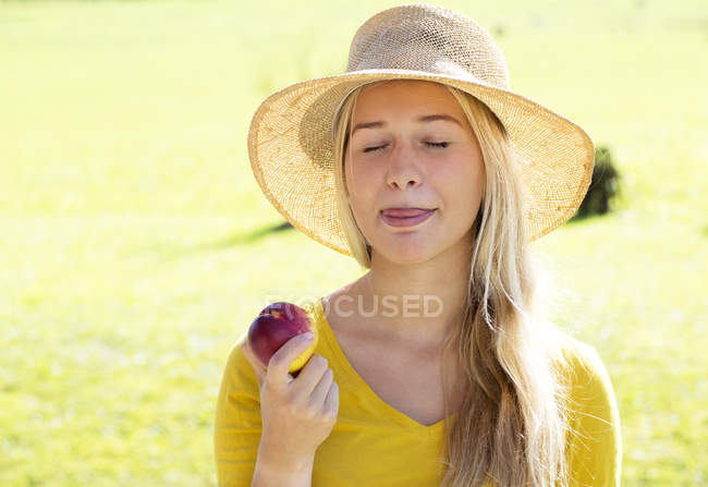 Portrait of smiling teenage girl eating a peach — Stock Photo
