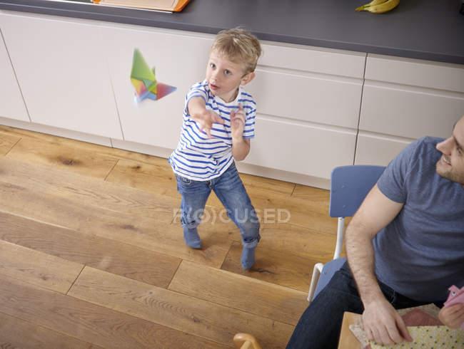Petit garçon avec avion en papier coloré à la cuisine — Photo de stock