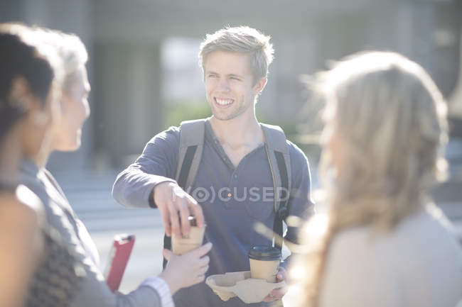 Young man distributing coffee to go to friends — Stock Photo