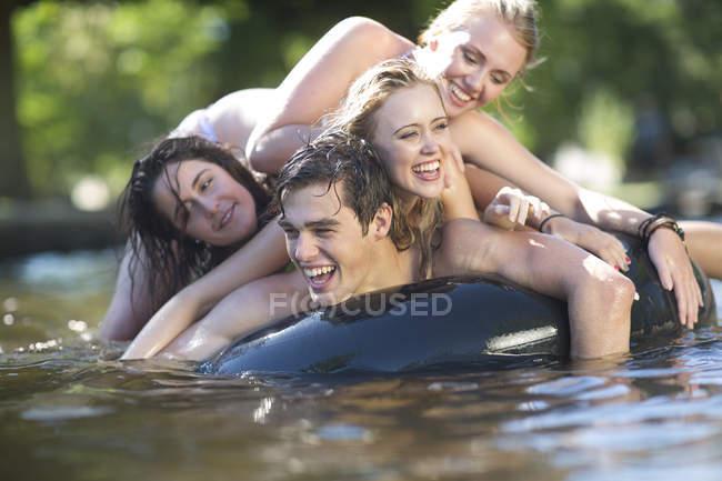 Amigos em férias se divertindo com tubo interno em uma piscina — Fotografia de Stock