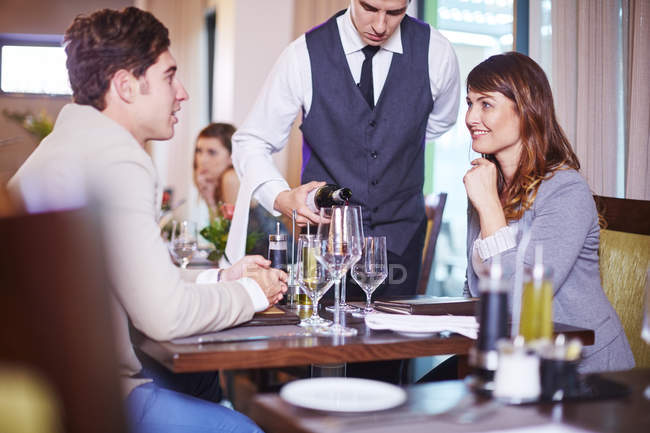 Waiter pouring wine for business associates at hotel restaurant — Stock Photo