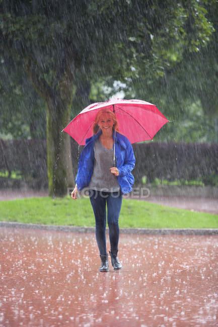 Дівчинка-підліток з червоним парасолька гуляти під дощем — стокове фото