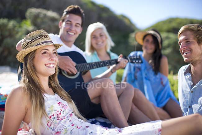 Amis socialiser sur la plage et jouer de la guitare acoustique — Photo de stock