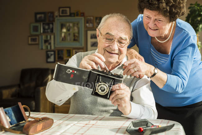 Senior couple with old camera at home — Stock Photo
