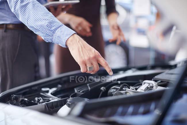 Concessionario auto spiegando motore auto — Foto stock