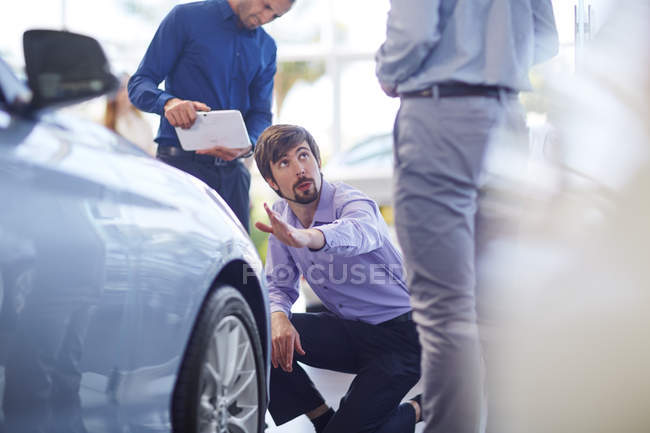 Car dealer talking to clients — Stock Photo