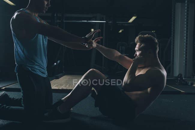 Два друга тренируются вместе в тренажерном зале — стоковое фото