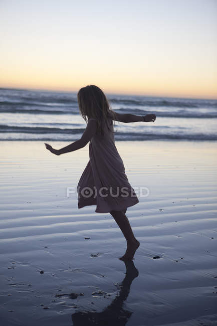 Little girl at beach dancing in evening twilight — Stock Photo