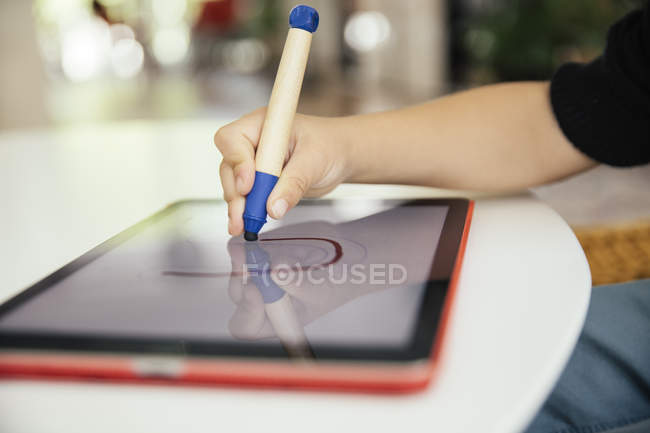 Hand of child drawing letter with a digital pen on digital tablet — Stock Photo