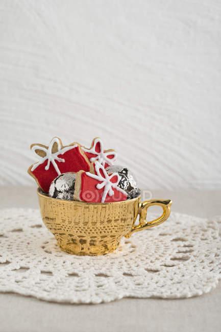 Biscoitos de Natal em copo dourado, toalha de mesa de crochê — Fotografia de Stock