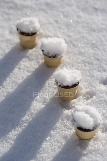 Cuatro conos de helado pegados en la nieve - foto de stock