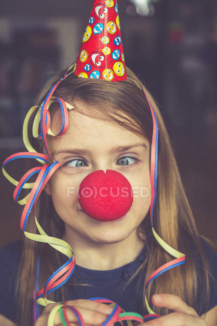 Cross-eyed girl with clown nose, cap and streamer — Stock Photo