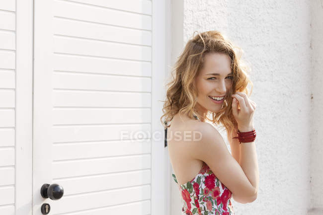 Portrait of smiling young woman with curly hair — Stock Photo