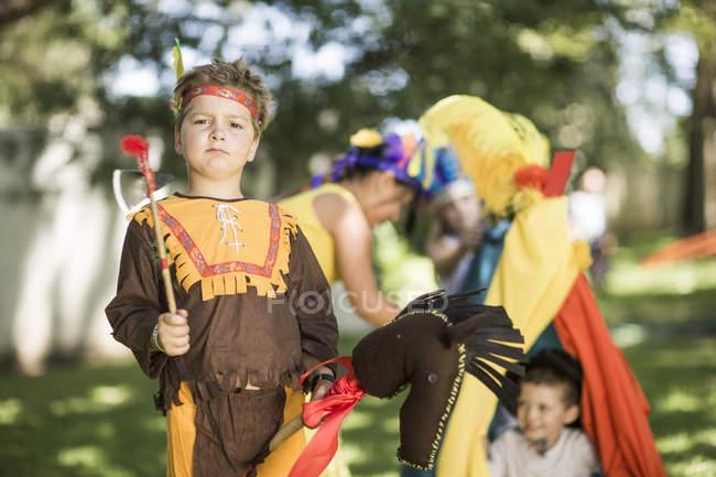 Портрет мальчика в саду, играющего в ковбоев и индейцев — стоковое фото