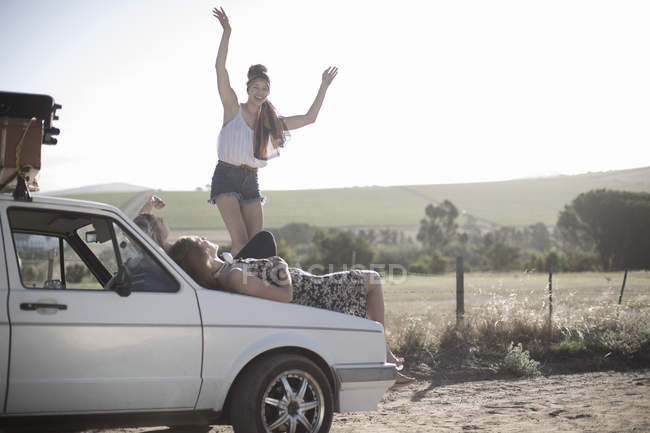 Friends on a road trip resting on car bonnet — Stock Photo