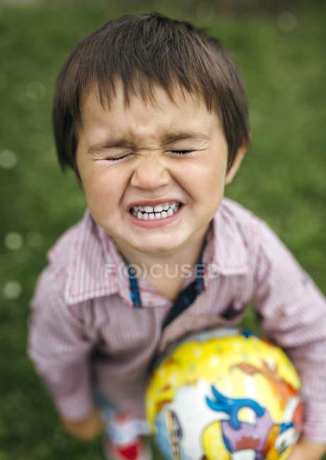 Kleinkind-Junge mit Ball ballte Zähne mit geschlossenen Augen — Stockfoto