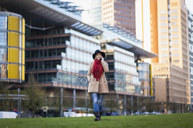Mujer joven con sombrero negro y bufanda roja telefoneando con teléfono inteligente - foto de stock