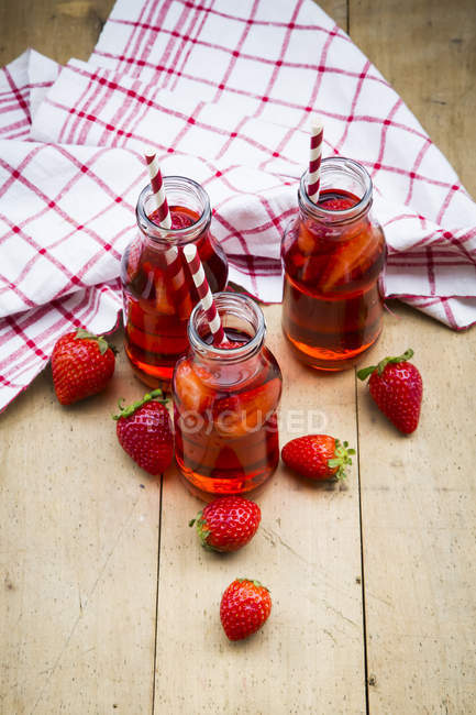 Elevated view of three glass bottles of homemade strawberry lemonade on wooden table — Stock Photo