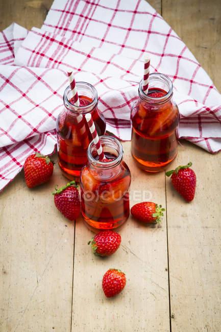 Vue surélevée de trois bouteilles en verre de limonade à la fraise maison sur table en bois — Photo de stock