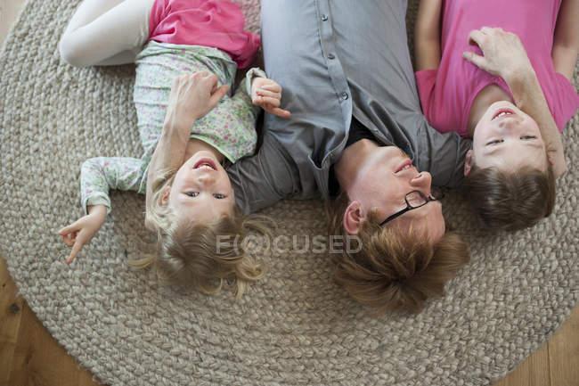 Батько з двох дочок, лежить на підлозі будинку — стокове фото