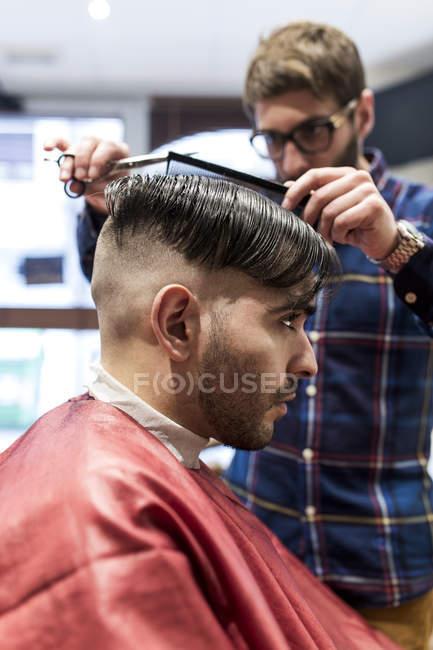 Parrucchiere che taglia i capelli di un giovane in un barbiere — Foto stock