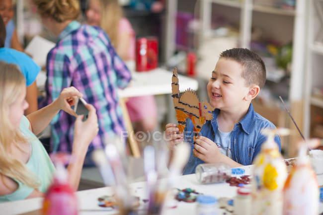 Улыбающийся мальчик в классе искусств держит произведение искусства — стоковое фото