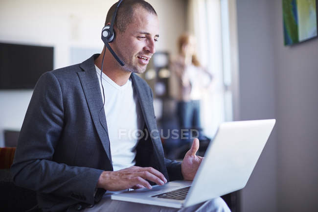 Businessman with headset using laptop in hotel room — Stock Photo