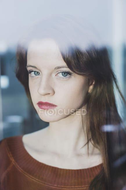 Ernsthafte junge Frau hinter Fensterscheibe — Stockfoto