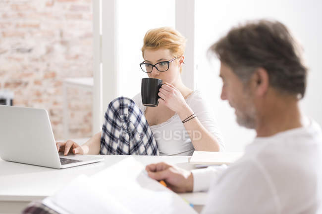 Jeune femme en pyjama à l'aide d'un ordinateur portable avec homme lecture — Photo de stock