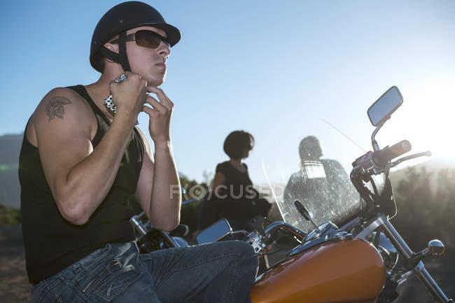 Homme sur attacher la sangle de casque de moto — Photo de stock