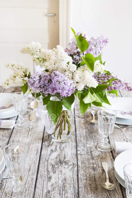 Table dressée en bois avec lilas blanc et violet — Photo de stock