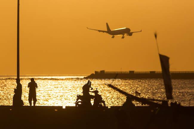 Indonésia, Bali, Jimbaran, pôr do sol no oceano com avião no céu — Fotografia de Stock