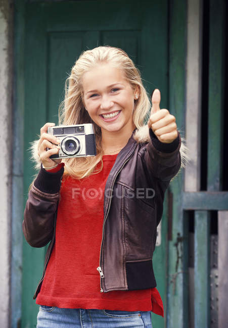 Portrait of smiling teenage girl with old camera and thumb up — Stock Photo