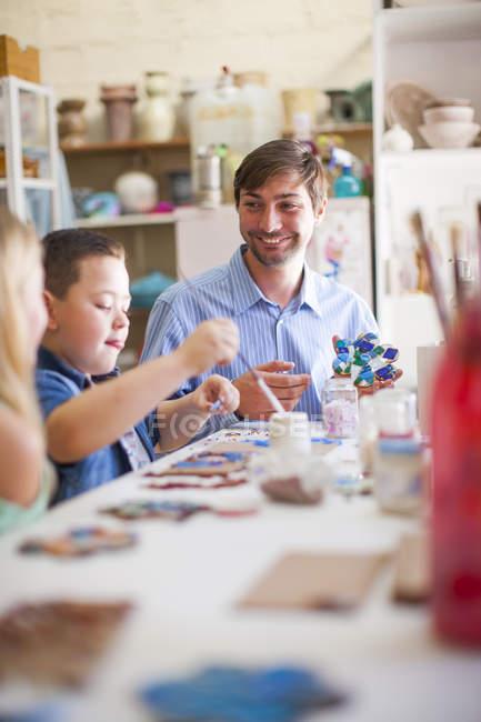 Insegnante maschio guardando i bambini nella classe di arti — Foto stock