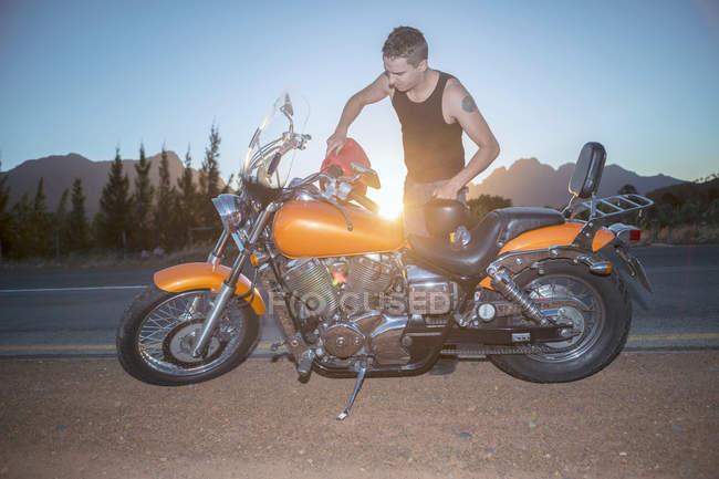 Biker refueling motorcycle by the roadside — Stock Photo