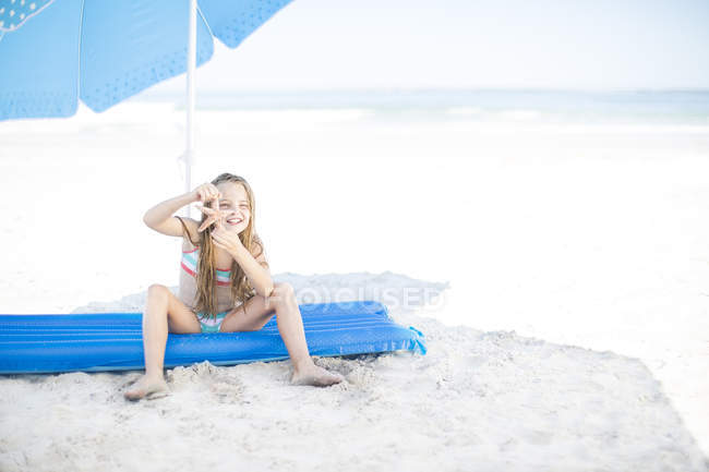Girl on beach sitting on a lilo holding a starfish — Stock Photo