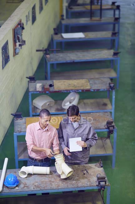 Bauarbeiter und Polier diskutieren über Rohrleitungen — Stockfoto
