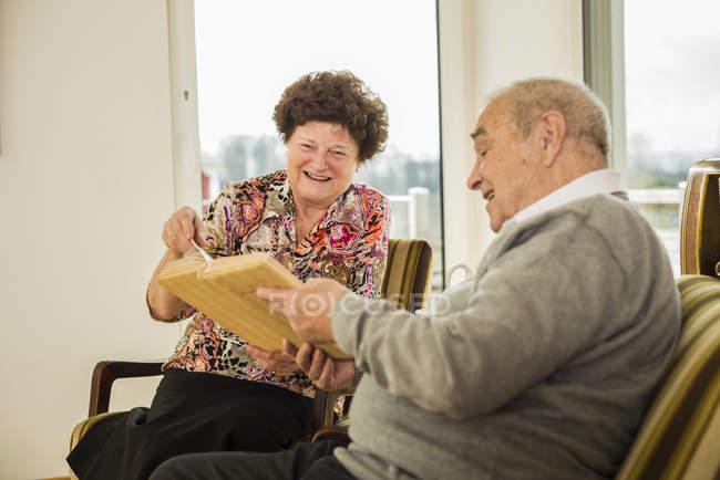 Album photo regarder de couple de personnes âgées — Photo de stock