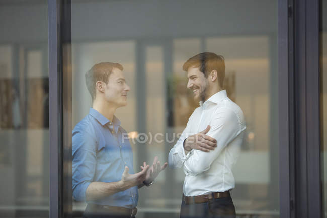 Two businessmen communicating behind window in office — Stock Photo