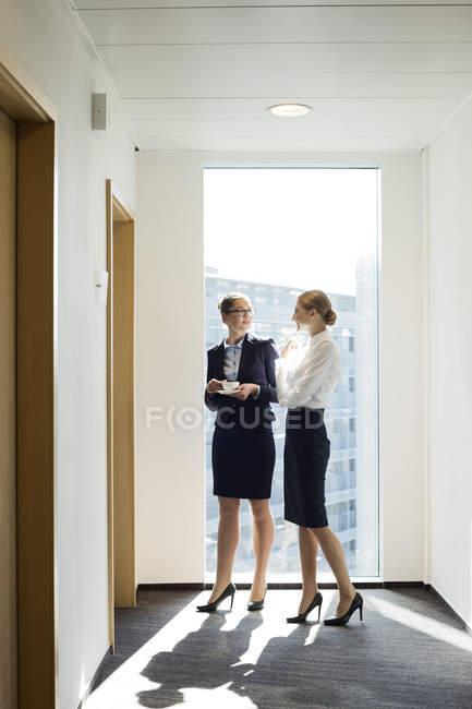 Два улыбаясь предпринимателей, говорят в коридоре — стоковое фото