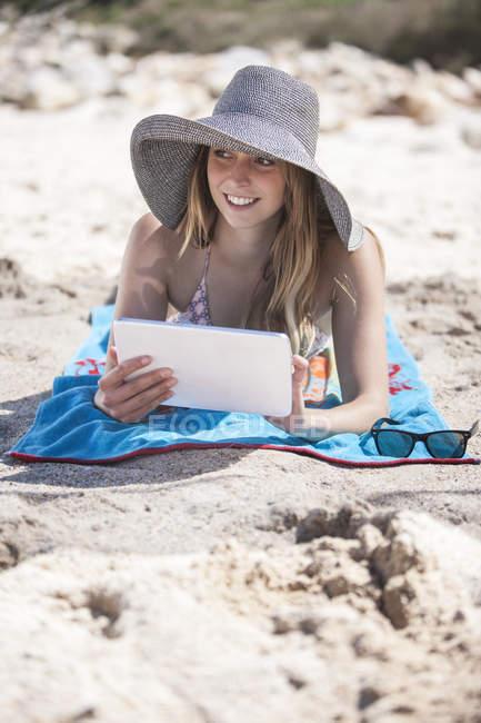 Усміхаючись молоду жінку, використовуючи цифровий планшет на пляжі — стокове фото